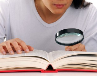 Mujer leyendo un libro sujetando una lupa.