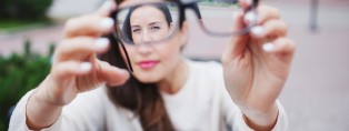 Closeup portrait of young women with glasses. She has eyesight problems and is squinting his eyes a little bit. Beautiful girl is holding eyeglasses right in front of camera with two hand